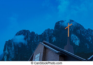 Cross on church with dark hill background.