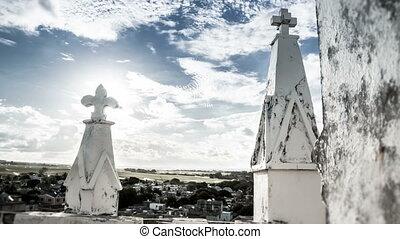 cross on mauritian church with sun reflecting