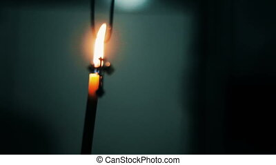 Cross on the background of a burning candle in the church