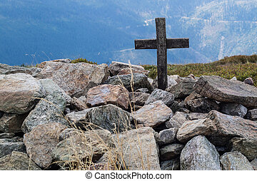 Cross on the top of a mountain in central europe. A wooden sign of Christianity lined with stones.