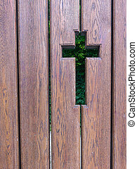 Outline of a cross on brown wooden gate.