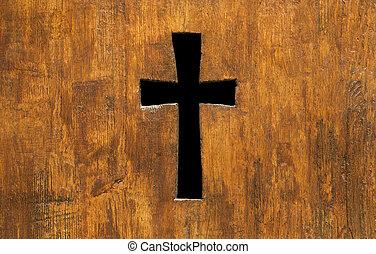 Cross shape hole in a church wooden fence