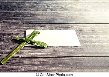 Cross shape of palm leaf on wooden table. Palm Sunday concept