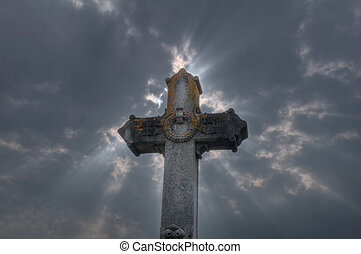 Cross shape - Ancient cross in a cemetery with a dramatic...