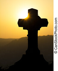Cross silhouette against a sunset
