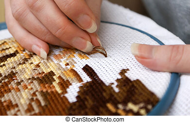 Cross-stitch - Woman's hands embroidering a picture...