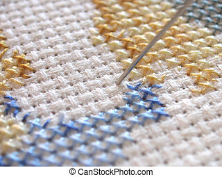 cross-stitch work - needle just going through the work of a...