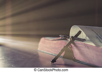 Cross with Bible on a old oak wooden table. Beautiful dark background. Religion concept