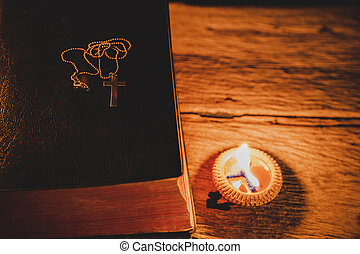 Cross with Holy Bible and candle on a old oak wooden table.