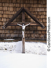 cross with jesus christ figur at a bavarian farmhouse in winter