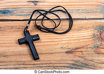 Cross with leather cord on a wooden texture background