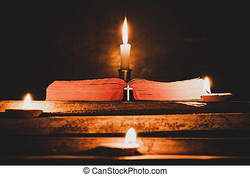 Cross with Open Holy Bible and candle on a old oak wooden table. Beautiful gold background. Religion concept.