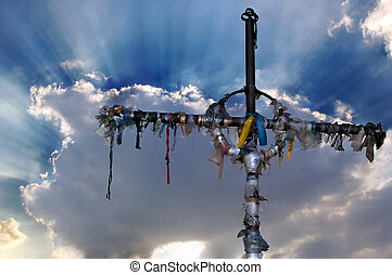 Cross with ribbons against clouds