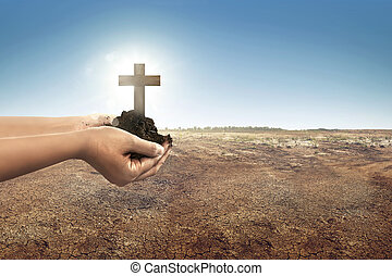 Cross with soil in human hands on the land