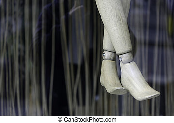 Crossed legs of wooden puppet in shop window