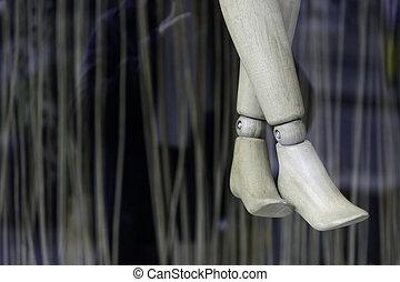 Crossed legs of wooden puppet in shop window