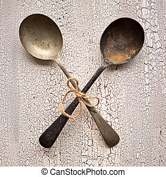 Crossed Old vintage spoons on white wooden background, top view