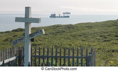 Crosses on the graves in the background of the ocean.