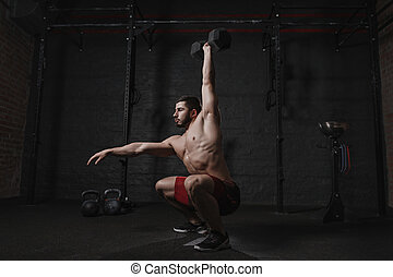 Crossfit athlete exercising at the gym doing overhead