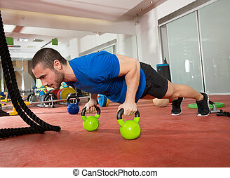 Crossfit fitness man push ups Kettlebells pushup exercise at...