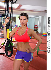 Crossfit fitness woman standing at gym holding trx