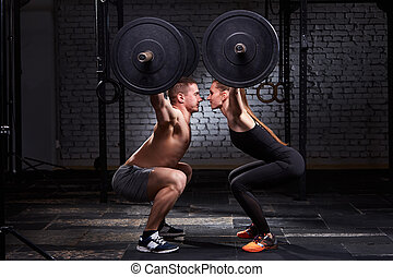 Crossfit lifting bar by woman and man in group workout...