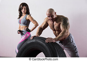 CrossFit training. Woman and man with tire.