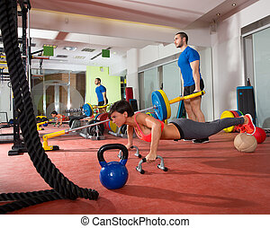 Crossfit woman push ups exercise and man weight lifting -...