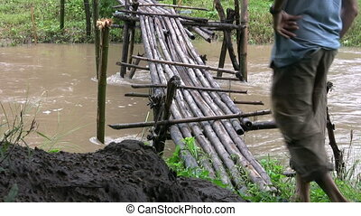 Crossing A Rickety Old Bridge - A man carefully crosses a...