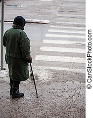 Crossing a slippery street - Older person crossing a...