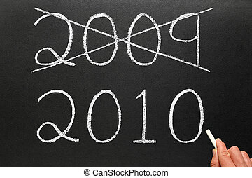 Crossing out the old year 2009 and writing 2010 on a ...