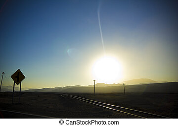 Crossing railroad tracks, sunset in the Andes, Atacama, Chile.