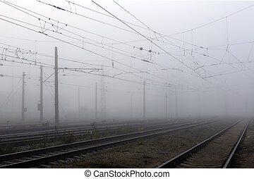 Crossing railways disappearing in the mist in autumn morning...