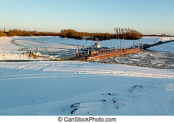 A boat on a frozen river supports the pontoon for crossing to the other shore