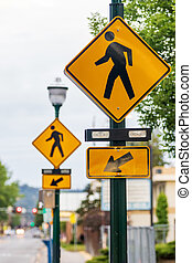 Crosswalk signs on a lamp post with arrows and a man symbol