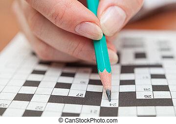 Crossword puzzle close-up.Hand doing crossword