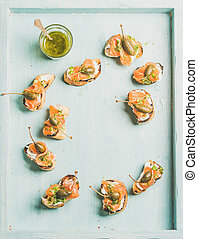 Crostini with smocked salmon, pesto sauce, watercress, capers. Top view