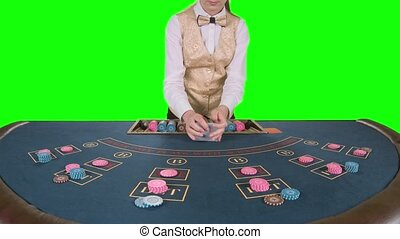 Croupier cleverly handling playing cards at a poker table. Green screen. Slow motion