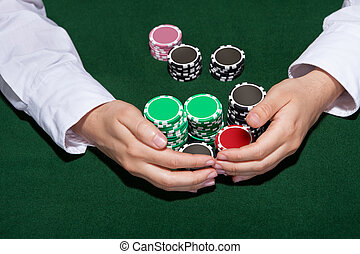 Croupier collecting in the bets at a casino table with his hands encircling various stacks of tokens or chips