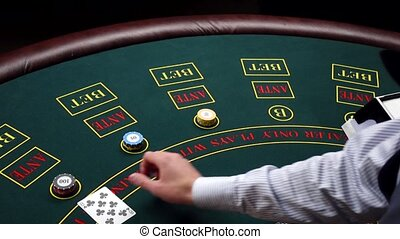 Croupier deal cards on green table with chips at casino -...