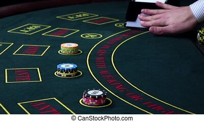 Croupier deal cards on green table with chips, slow motion