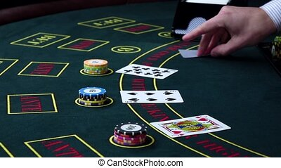 Croupier deal cards on poker table with chips, slow motion