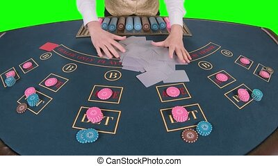 Croupier handling playing cards at a poker table. Green...