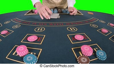 Croupier professionally handling playing cards at a poker table. Green screen. Slow motion. Close up