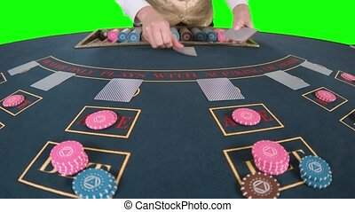 Croupier professionally handling playing cards at a poker table put three cards are the flop in front of him. Green screen. Slow motion. Close up