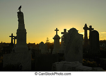 dusk at cemetery, crow sitting on tombstone, several grave silhouettes