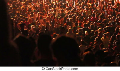 Crowd of people raising their hands and applauding at a concert