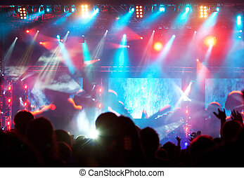Crowd at concert in colorful stage lights