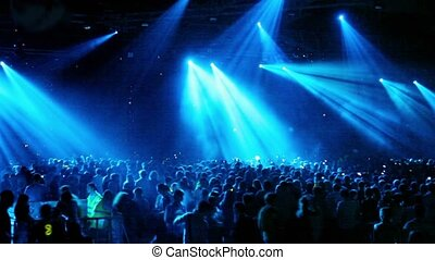 Crowd at rave party, people dance in blue light of...