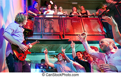 Crowd going wild during a live performance of a guitarist in...